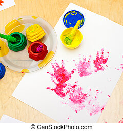 Fingerpaint - White paper with child handprints on on a...