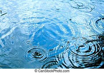 Rainy weather - Rain drops rippling in a puddle with blue...