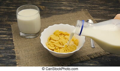 fresh milk pouring into a bowl full of cornflakes in...