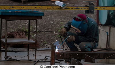 Worker welds metal for construction - Worker welds metal...