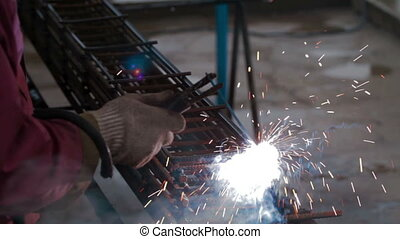 Worker welds metal grid for construction - Metal welding...