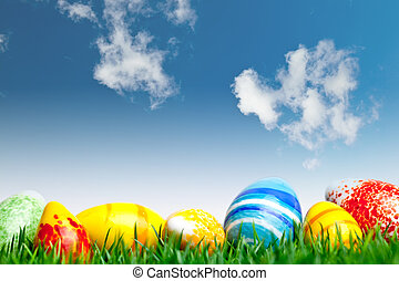 Easter eggs in green grass over blue sky with clouds