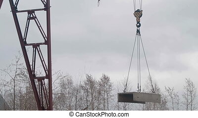 Crane lowers concrete slab - Concrete slabs hang on...