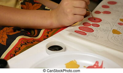 Child paints watercolor picture with paint brush -...