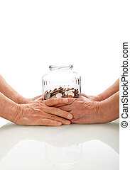 Senior hands holding a jar with coins - retirement fund...