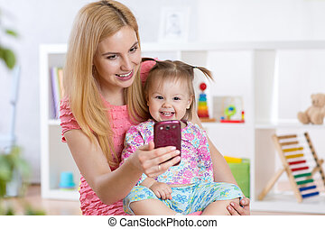 Mother and her  little child girl taking selfie on a blanket in nursery room