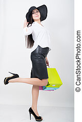 Full length of a beautiful young asian lady in a white blouse and black leather skirt holding colorful bags. Girl goes shopping
