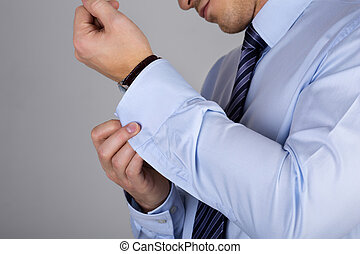 Man fastens his cuff links close-up Businessman or fiance...