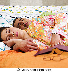 Couple Sleeping On Bed - A man and woman sleep on a bed with...