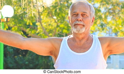 Old Man Does Morning Exercises Lifts Hands up in Park -...