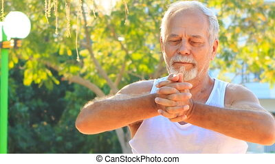 Old Man Does Morning Exercises Stretches Fingers in Park -...