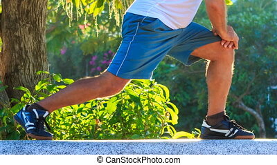 Closeup Man Does Morning Exercises Squats on Knee in Park -...