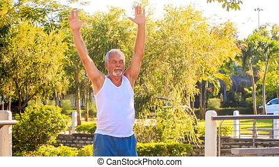 Old Man Does Morning Exercises Turns Right Left in Park