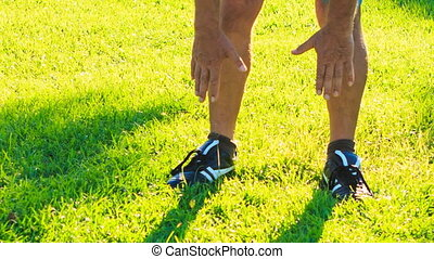Man Does Morning Exercises Bends to Feet on Green Grass Lawn...