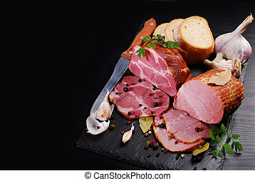 pieces of homemade smoked pork ham on black background and...