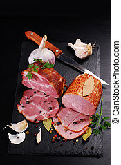 pieces of homemade smoked pork ham on black background -...