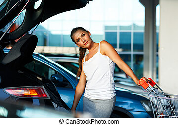 Woman shifts the purchase from shopping cart in the trunk of...