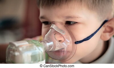 Child with inhaler 4 - The little boy makes treatment...