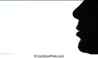 Adult man is smoking, close up, silhouette, on white...