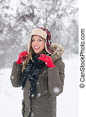 girl smiling in the snow wearing a lumberjack hat