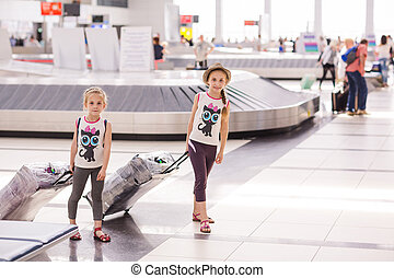 Happy kids with luggage inside airport going on vacations...