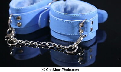 blue leather handcuffs in black background sex toy - blue...