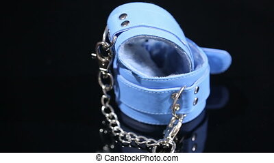 blue leather handcuffs in black background. sex toy - blue...