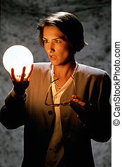 Businesswoman Gazing Into Glowing Ball - A businesswoman...