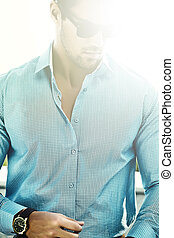 Fashion portrait of young sexy handsome model man in casual cloth in sunglasses in the street behind sun