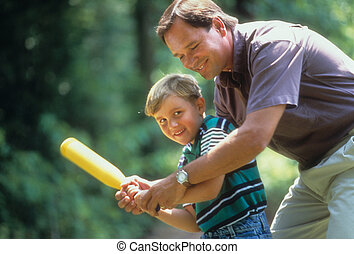 Father Showing Son How to Hold a Bat - Cropped image of a...
