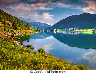 Sunny summer scene on Resia lake Resia village in the...
