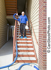 Carpet Cleaning - Man cleaning carpet with commercial steam...
