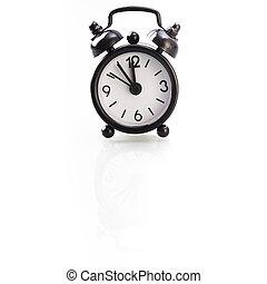 Black alarm clock showing five to twelve