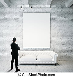 Man in modern suit looking at empty canvas holding on the...
