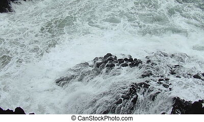Waves breaking by stones. Slow motion