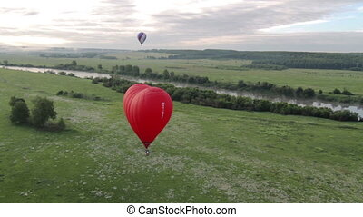 Flight of behind red hot air balloon