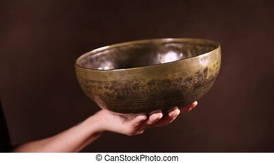 Video shot of Tibetan singing bowl in ones hand in front of...