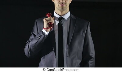 man in a business suit holding a whip for sex games. red...