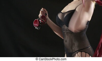 Busty girl in lingerie shows Red handcuffs on black...