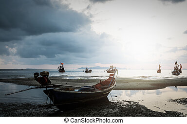 Many fishing boat in the sea when low tide under the...