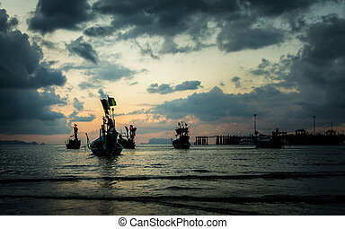 Many fishing boat in the sea when low tide under cloudy sky...