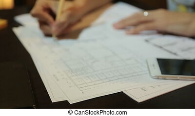 Women architect working with blueprint sheets, layouts and drawings of the premises. Woman in work.
