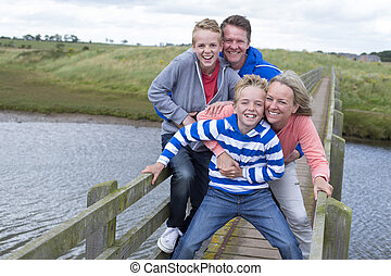 Happy Family of Four - Family of four on a bridge over...