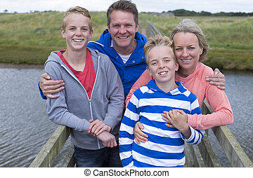 Happy Family of Four standing on a bridge over water. They...