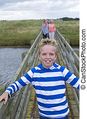 Front of The Family - Portrait of a young boy on a bridge...