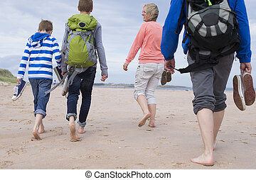 Barefoot Beach Day - Family of four walking along the beach...