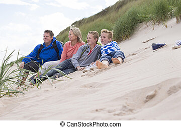 Family resting time - Family of four sitting on the sand...