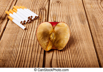 Concept of bad habits - Withered apple and cigarettes...