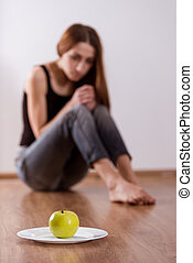 She refuses to eat - Thin girl refuses apple, located in the...