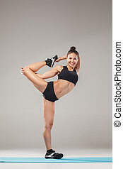 Beautiful sporty girl standing in acrobat pose or yoga asana...